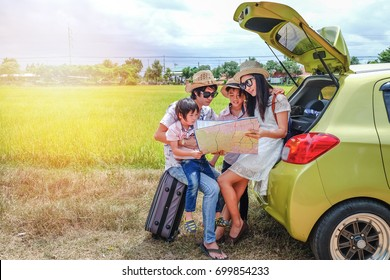 family of traveler sitting near their car and using local map for searching their way.Asia tourist look at the local map for find the way to go to destination.