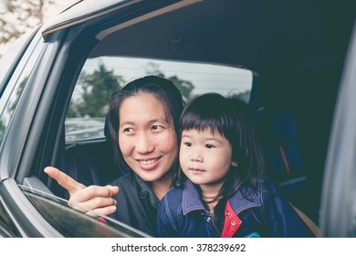 Family traveling by car. Asian mother and little lovely daughter travel on vacation. Happy parent and kid have fun. Outdoors.