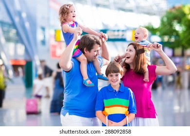 Family traveling with kids. Parents with children at international airport with luggage. Mother and father hold baby, toddler girl and boy flying by airplane. Travel with child for summer vacation.