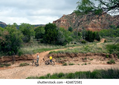Family traveling on bicycles stopped before the obstacle. Palo Duro Canyon State Park, Texas, US