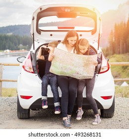 Family travelling by car and using paper map to navigate sitting in open trunk