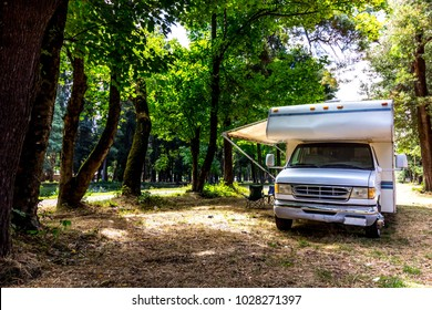 Family trip in motorhome in forest or park in south chile.