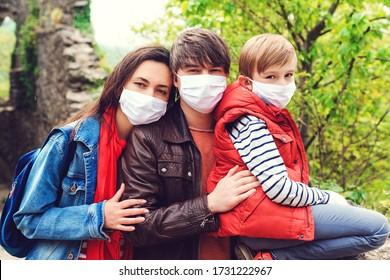 Familienausflug in die alte Burg. Coronavirus-Quarantäne. Eltern mit Sohn tragen im Freien Gesichtsmasken. Familienspaziergang in der Nähe von Burgruinen. Reisen während einer Koronavirus-Pandemie.
