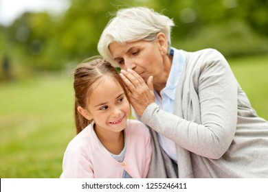 family, trust and people concept - happy granddaughter whispering secrets to grandmother at summer park