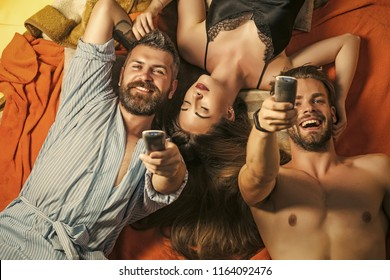 Family trust, polygamy, betrayal. people lovers with remote controle. Love triangle and romance, perfect morning. Swinger relations, relax, wake up. men and woman with long hair watch tv. friends