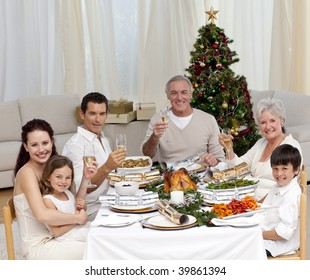 Family tusting with white wine in a Christmas dinner at home