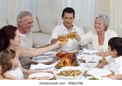 Family tusting with wine in a dinner at home
