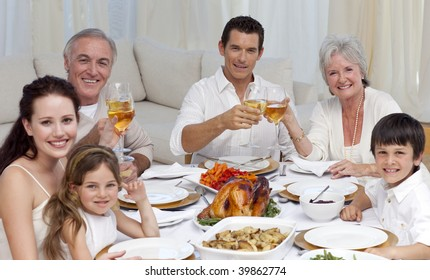 Family tusting with wine in a dinner at home smiling at the camera