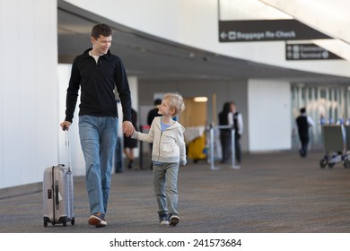 family of two at the airport with luggage
