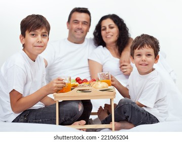 Family with two boys having breakfast in bed - with parents in background