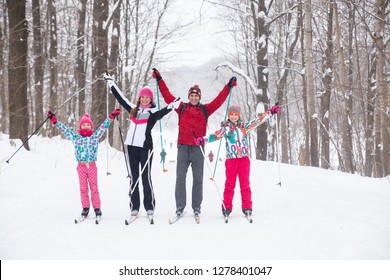 Family with two children cross-country skiing in the winter forest in the snow