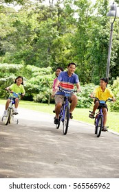Family with two children, cycling side by side