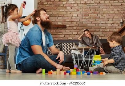 Family with two children having fun at home, playing together.