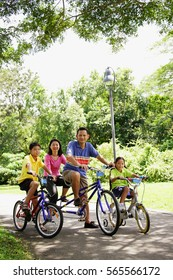 Family with two children, on bicycles, portrait