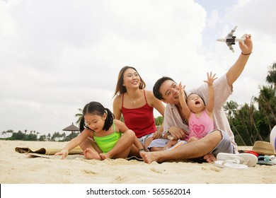 Family two children, playing on beach with toy boat and toy plane