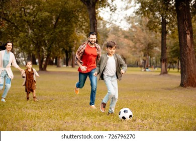 Family with two children running and playing soccer together in an autumn park