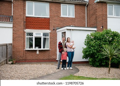 Family with two children standing and looking at the camera while smiling outside their house. They are proud owners of their home.