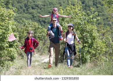 Family with two daughters travels along a beautiful path in the forest