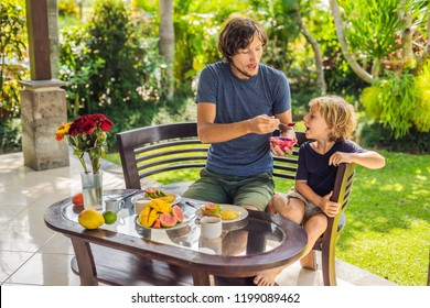 family of two eating nicely served breakfast outside handsome young man pouring some coffee and his cute son eating delicious fruit at breakfast time.