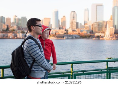 family of two enjoying ferry boat ride in seattle with great city skyline view at sunset