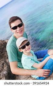 family of two enjoying rocky beach at grand cayman, cayman islands, caribbean