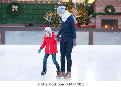 family of two enjoying winter vacation at outdoor cozy skating rink at christmas time and learning ice skating