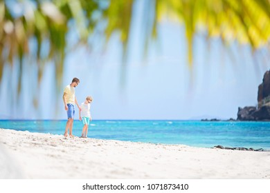 family of two, father and son, enjoying white sand beach at beautiful tropical fiji island, vacation concept