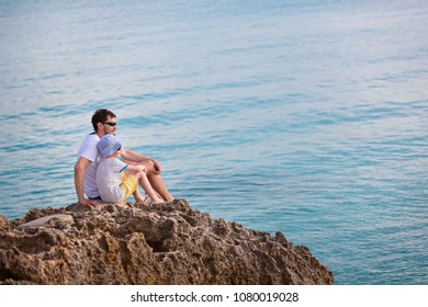family of two, father and son, enjoying sunset together sitting at the rock at anguilla island, caribbean, copy space on right