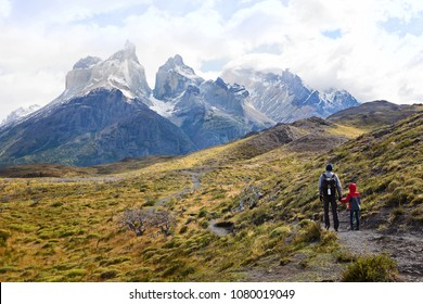 family of two, father and son, enjoying gorgeous view of cuernos del paine in torres del paine national park in chile, active family vacation concept