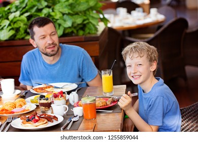 family of two, father and son, enjoying scrumptious breakfast together, breakfast at home or at luxury resort at tropical vacation