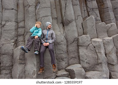 family of two, father and son, enjoying beautiful basalt columns of gardar at reynisfjara black sand beach near vik in iceland, family adventure and active vacation concept