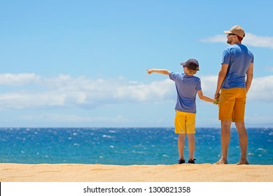 family of two, father and son, enjoying their vacation together at the beautiful polihua beach at lanai island, hawaii, family activity concept, copy space on left