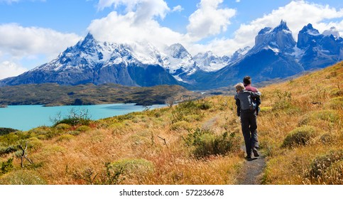 family of two, father and son, enjoying hiking and active travel in torres del paine national park in patagonia, chile, view of cuernos del paine and pehoe lake