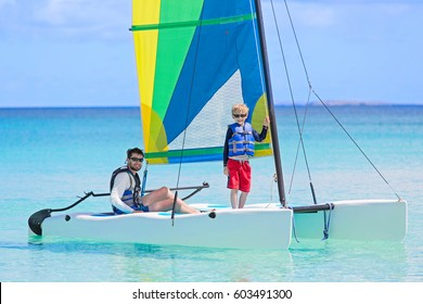 family of two, father and son, enjoying sailing together at catamaran, active healthy lifestyle