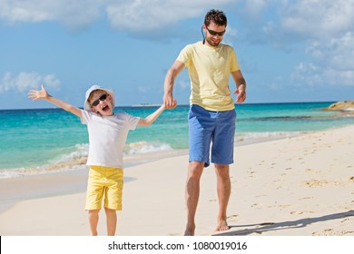 family of two, father and son, having fun at the beach together, family vacation concept