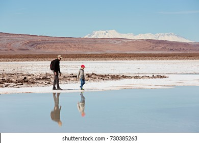 family of two, father and son, hiking and walking together enjoying salty lagunas escondidas in atacama desert, chile, healthy active family lifestyle and vacation concept