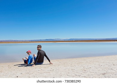family of two, father and son, ready to swim in salty cejar lagoon in atacama desert, chile,  healthy active family lifestyle and vacation concept
