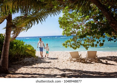 family of two, father and son, running on empty beautiful white sand beach with palm trees and turquoise lagoon, family vacation concept