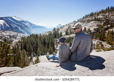 family of two, father and son, sitting and enjoying the view at beautiful mountains at tioga pass in yosemite national park, active vacation concept