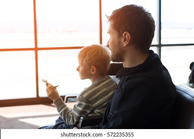 family of two, father and son, waiting together at the airport for plane departure, kid holding toy plane, sun flare, vacation and travel concept