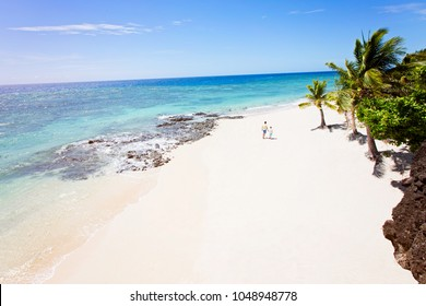 family of two, father and son, walking on empty beautiful white sand beach with palm trees and turquoise lagoon, family vacation concept, shot from above
