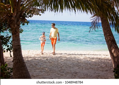 family of two, father and son, walking on empty beautiful white sand beach with palm trees and turquoise lagoon, family vacation concept