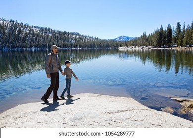 family of two, father and son, walking and enjoying beautiful tenaya lake at tioga pass in yosemite national park, active vacation concept
