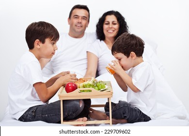 Family with two kids having a healthy breakfast in bed