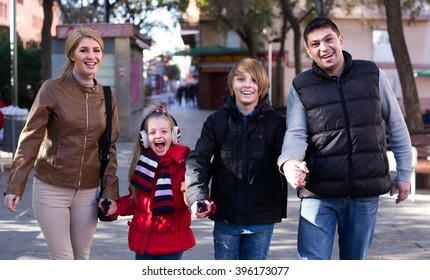 family with two kids having walk outdoors in autumn