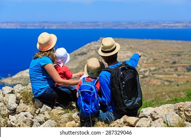 family with two kids looking at map in mountains, family travel