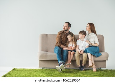 family with two kids sitting on couch and looking away on grey