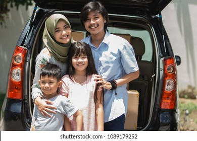 family with two kids smiling to camera ready to move to the new house