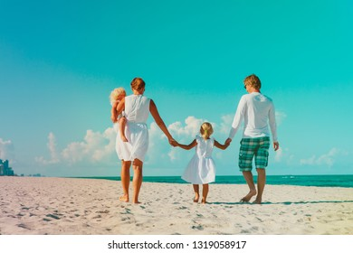 family with two kids walk on tropical beach