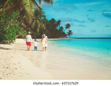 family with two kids walk on beach